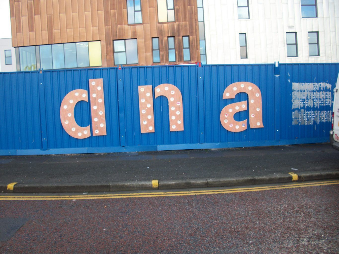 Fret cut timber letters fixed to metal hoarding -DNA