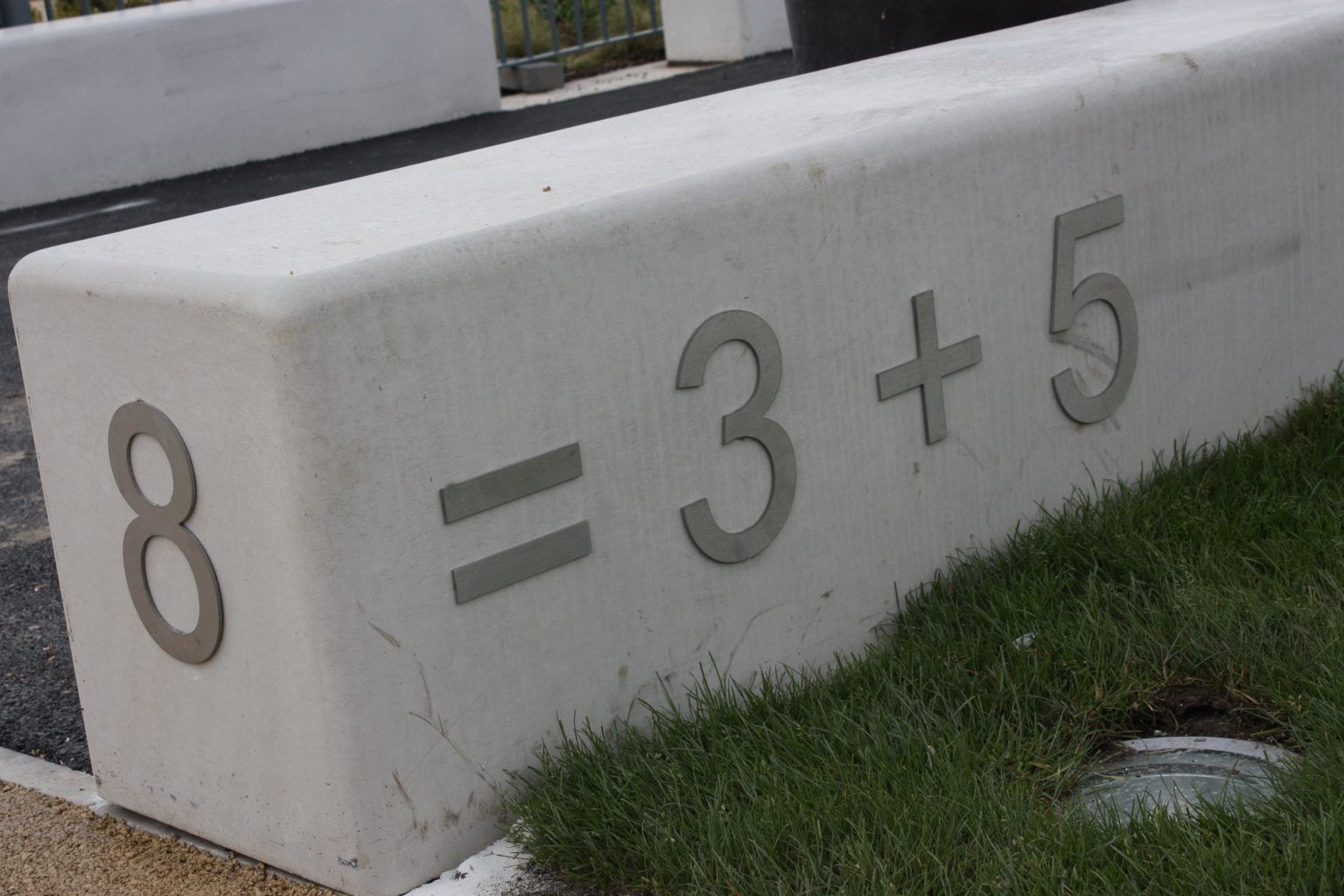 School flat cut Brushed Stainless Steel letters mounted to a concrete block